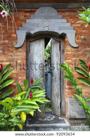 Balinese door surrounded by plants – Bali, Indonesia - stock photo