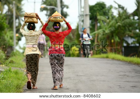 Balinese ladies carry offerings to the local temple - stock photo