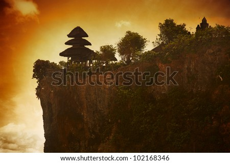 Balinese temple Uluwatu and dark yellow sky with clouds - stock photo