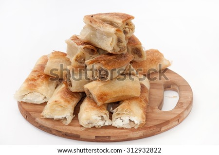 Balkan pie with cheese and Balkan meat pie on a wooden board. - stock photo