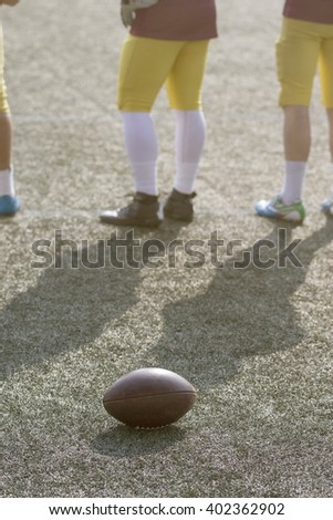 Ball and American football players on the field