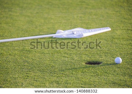 ball and flag on green of golf course - stock photo