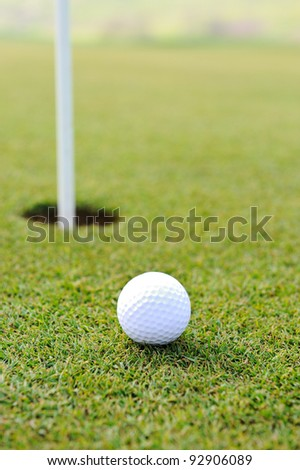 Ball and hole on golf field