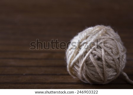 Ball of cream yarn on brown wooden background - stock photo