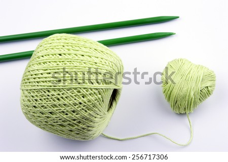 ball of knitting yarn forming a heart and knitting needle on white background - stock photo