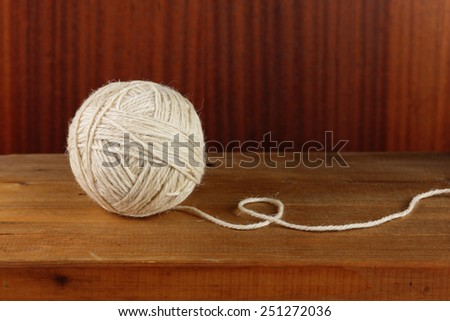 Ball of rough rustic yarn on dark wooden background - stock photo