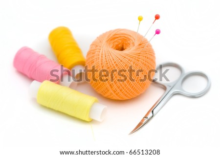 Ball of thread, scissors and a spool of colored thread on a white background - stock photo
