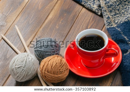 Ball of wool and Coffee on wooden floor, handmade - stock photo