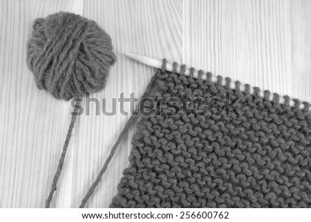 Ball of wool and garter stitch on a knitting needle - monochrome processing - stock photo