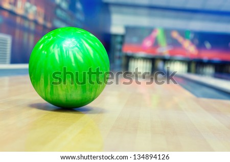Ball on bowling alley against ten pins