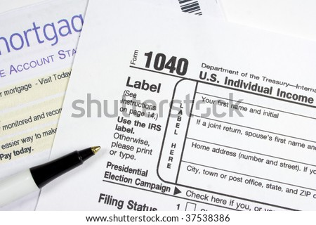 Ball point pen and US IRS 1040 form and mortgage statement - stock photo