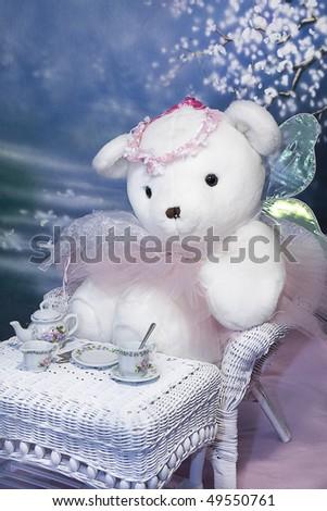 Ballerina/Angel Teddy Bear children's photo - Teddy having a bit of tea in white whicker set - stock photo