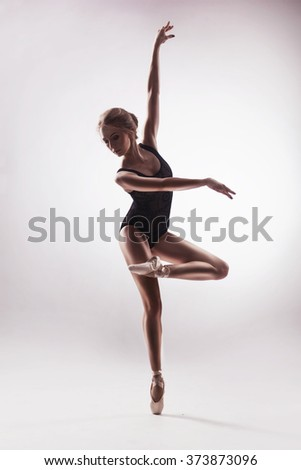Ballerina in beige outfit posing on toes - stock photo