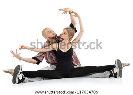Ballerina in black and bald breakdancer sit on floor and portray puppets isolated on white background. Woman stretched legs in twine. - stock photo