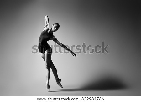 Ballerina in black outfit posing on toes, studio background. Grayscale image. - stock photo