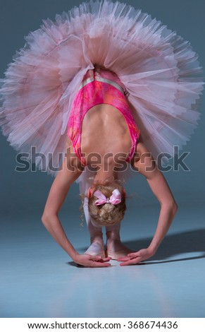 Ballerina in pink tutu  leaning forward - stock photo