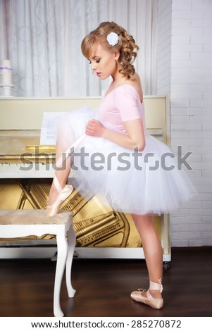 Ballerina in pointe shoes standing near the chair