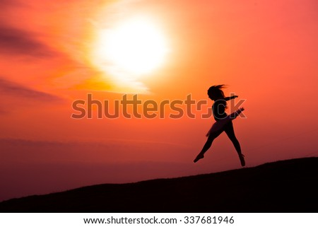 Ballerina in silhouette in a red sunset dance alone