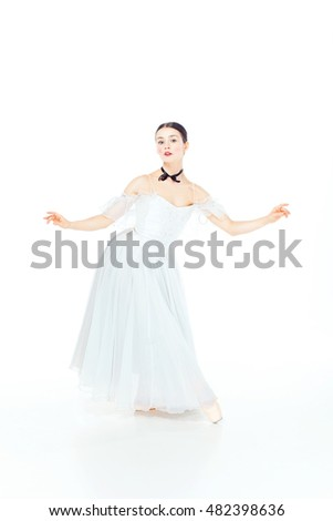 Ballerina in white dress posing on pointe shoes, studio white background.