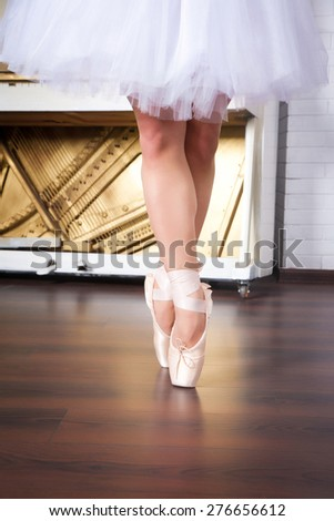 Ballerina legs in pointes in dancing hall, against the backdrop of the piano - stock photo
