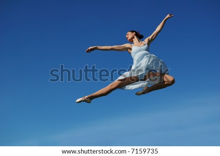 Ballerina performing a jump on a sunny day - stock photo