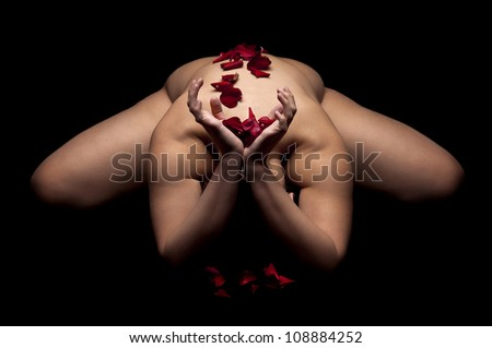 Ballerina posing in a dark background with rose petals - stock photo