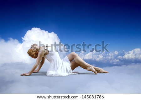 Ballerina seating on the sky clouds - stock photo