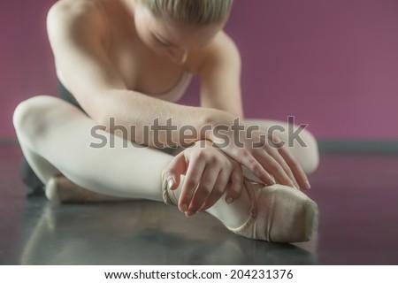 Ballerina sitting and bending forward in the ballet studio - stock photo