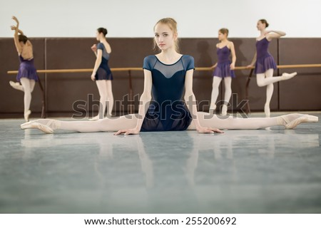 ballerina sitting on the floor front to the camera in the splits and dance class dancers practicing on the background - stock photo