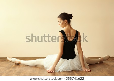 ballerina warming up in Pointes on wooden floor against a white background
