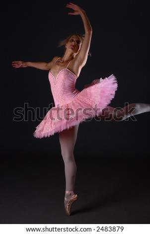 Ballerina with pink tutu jumping in the air while on one toe - stock photo