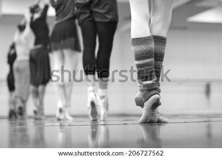 Ballerinas graciously standing on their toes in a row - stock photo