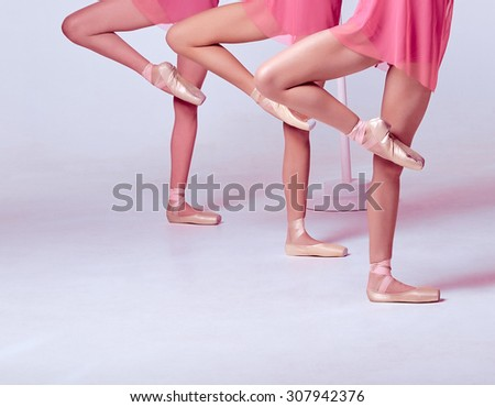 Ballerinas stretching on the bar - stock photo