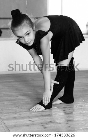 Ballet, ballerina - young and beautiful ballet dancer posing in dance studio. Black and white art photo with bokeh and grain. - stock photo