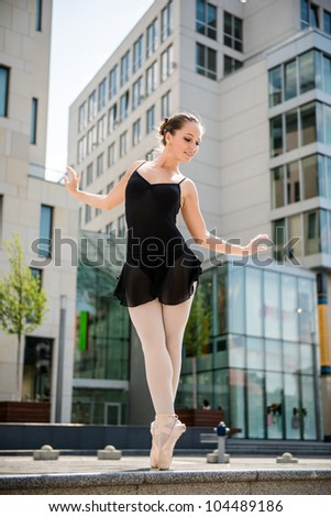 Ballet dancer (ballerina) dancing on street with business buildings in background - stock photo