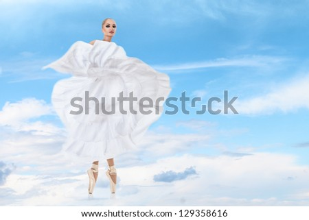 Ballet dancer in beautiful long white dress performing arts against high sky clouds - stock photo
