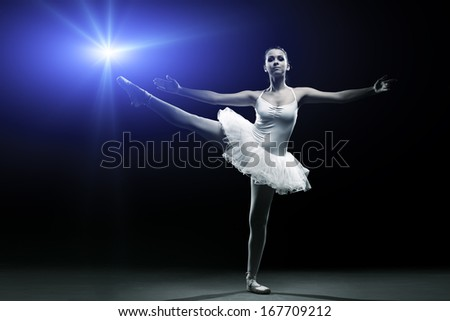Ballet dancer in white tutu posing on one leg - stock photo