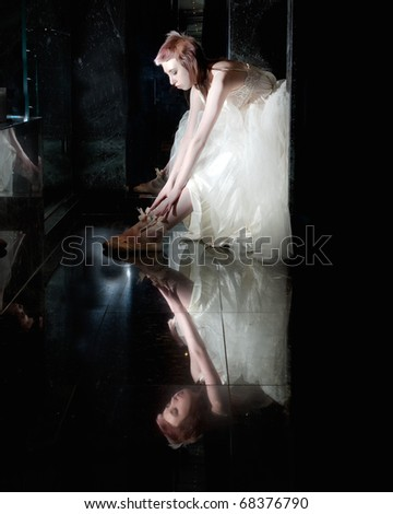 ballet dancer sitting in a tutu stretching on a black reflective background - stock photo