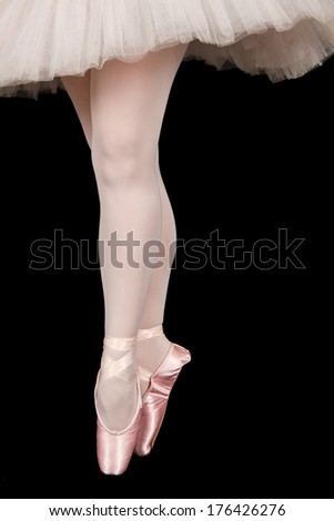 Ballet dancer standing on toes while dancing on black background in pink tutu - stock photo