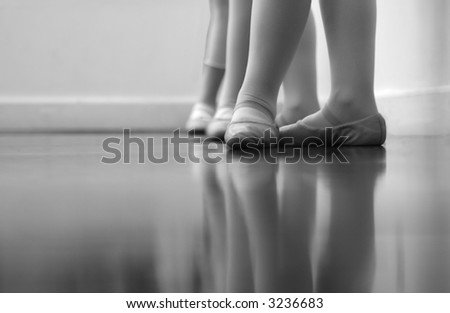 Ballet dancers feet and legs. Intentionally shot at high ISO to give a grainy, old time feel - with selective noise reduction applied. Black and white - stock photo