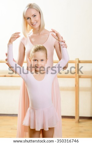 Ballet lesson. Young woman interacting with little girl during ballet lesson.