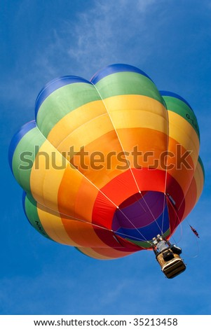 balloon flying into the bright blue sky on a bright sunny day in summer. photo was taken during the Bristol annual international hot balloon fiesta, uk. - stock photo