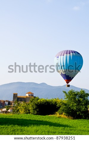 balloon flying over the village of Tortella, in the Catalan Pyrenees mountains. - stock photo
