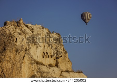 Balloon over fairy chimneys, typical rock formation in Goreme (Cappadocia), Turkey