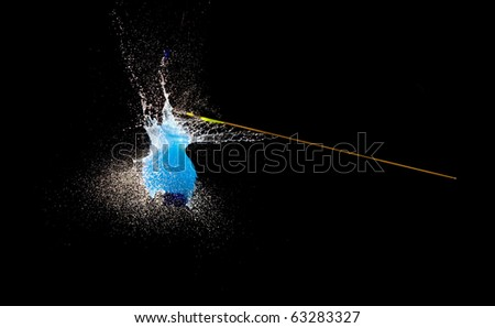 Balloon with water bursting punctured by arrow.High speed photography. - stock photo