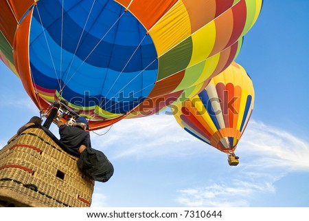 Balloonists running after another hot air balloon in a serene sky - stock photo