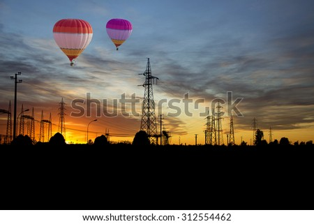 balloons over the electrical wires at sunset - stock photo