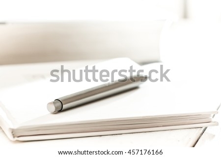 ballpoint metal pen on white notebook for records