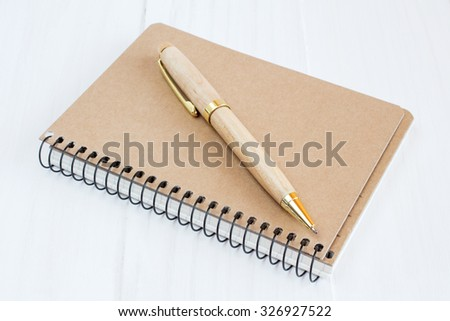 Ballpoint pen and brown cover notebook on wooden surface