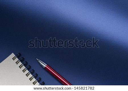 ballpoint pen and notebook on a blue background. - stock photo
